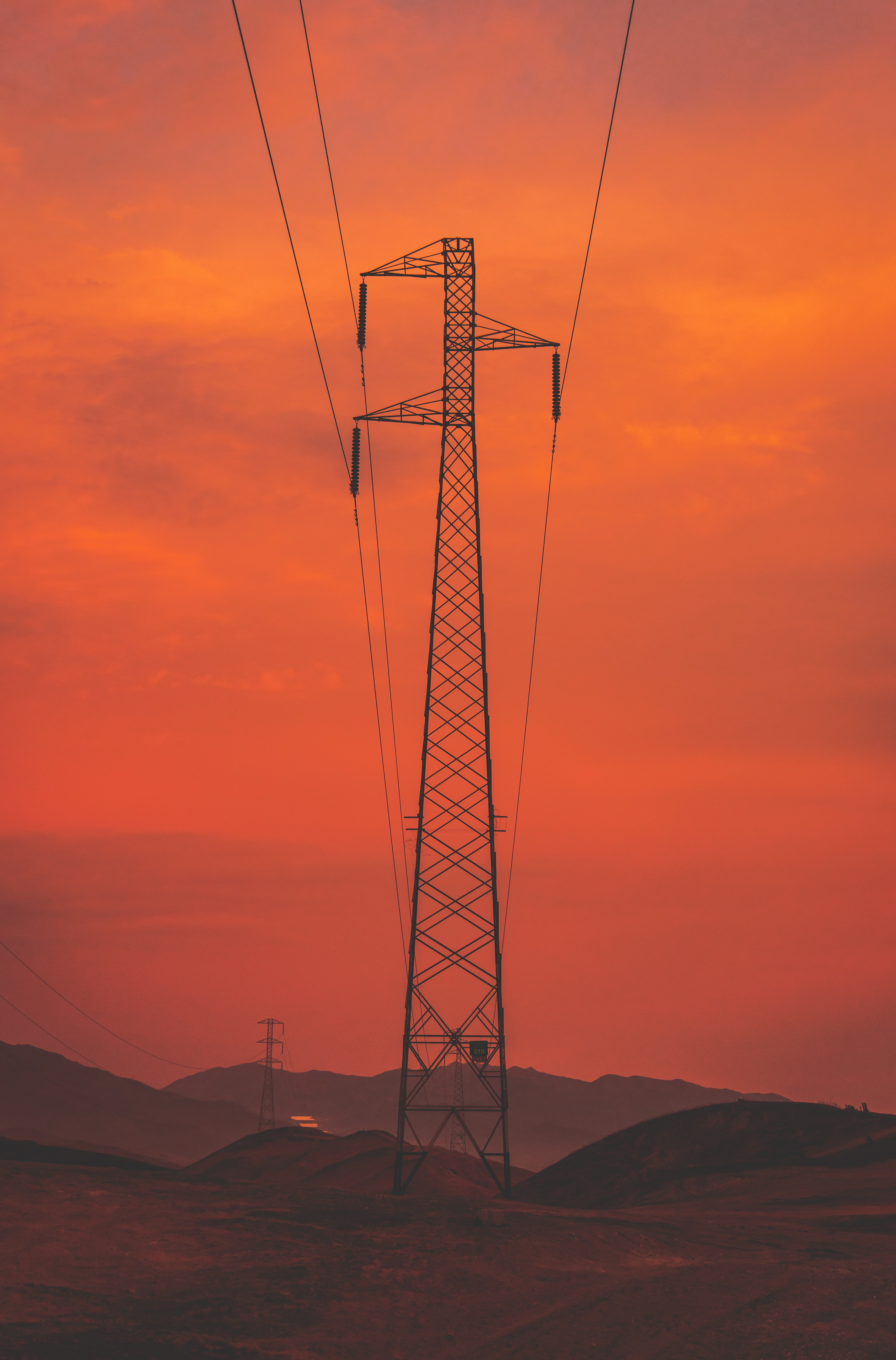 silhouette photography of electrical post during golden hour