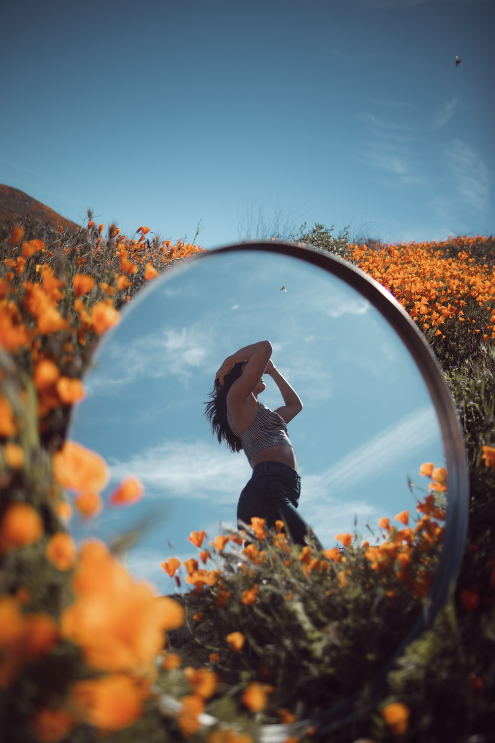 reflective photo of woman on flower garden