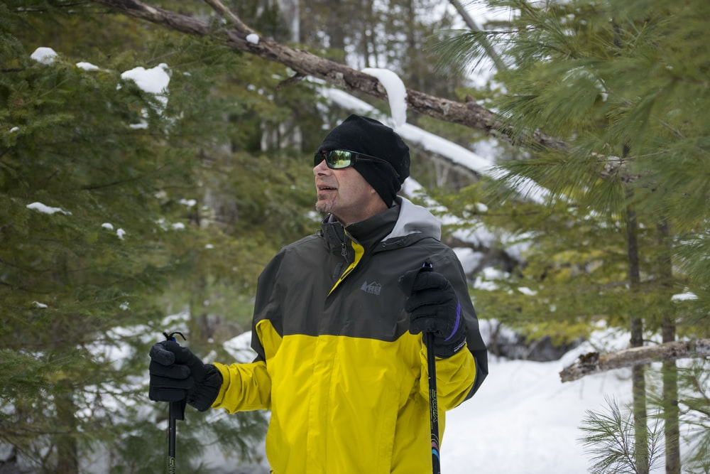 man in black and yellow jacket wearing black knit cap