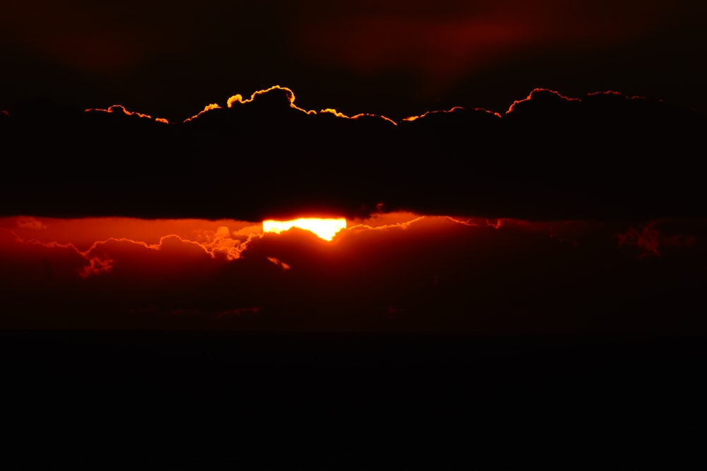 silhouette photography of sun behind clouds during golden hour