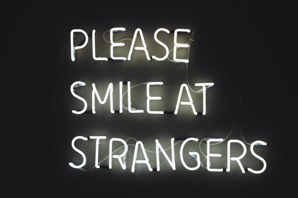 white LED light with text Please Smile at Strangers