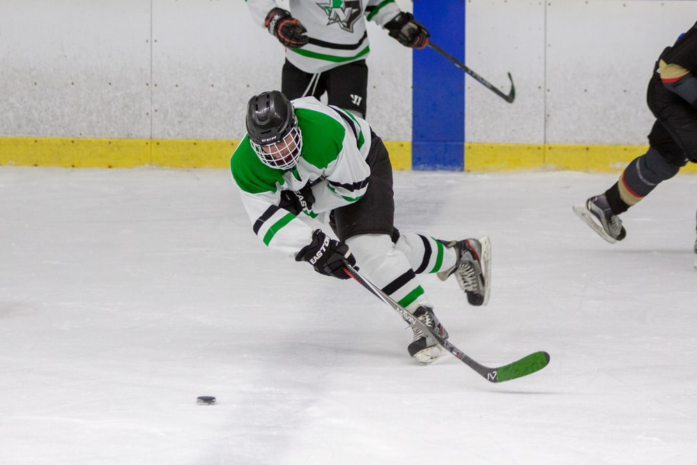 man in green and white playing ice hockey