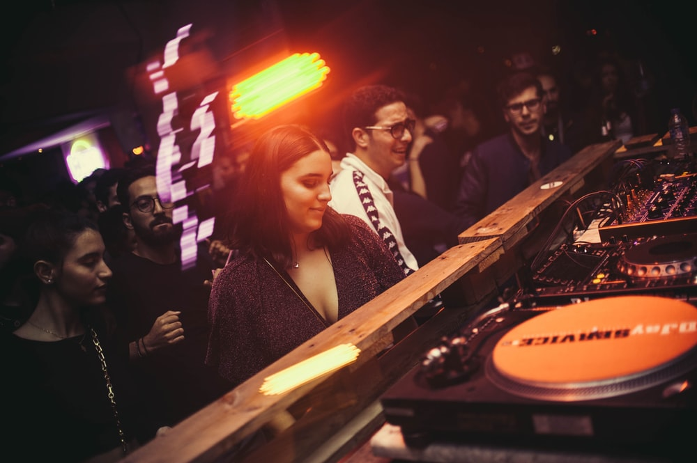 group of people standing in front of DJ controller