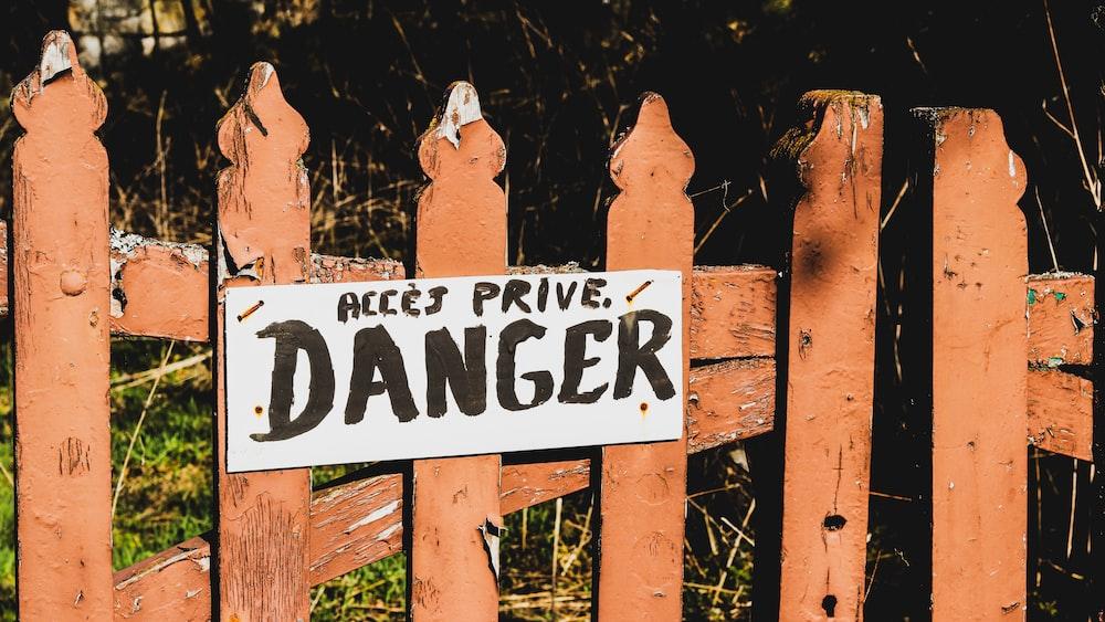 danger signage on brown wooden rail