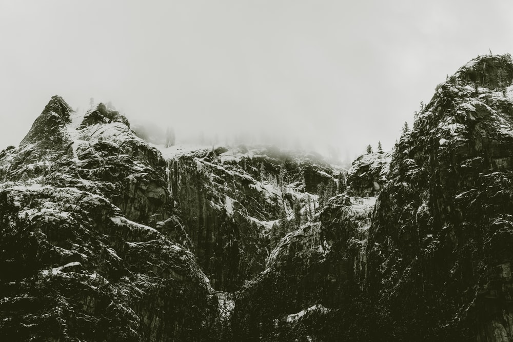 grayscale photo of mountain cover with snow