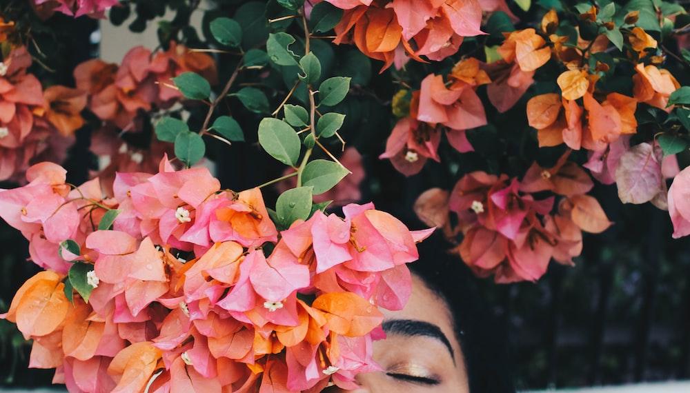 woman hiding behind bougainvillea flowers