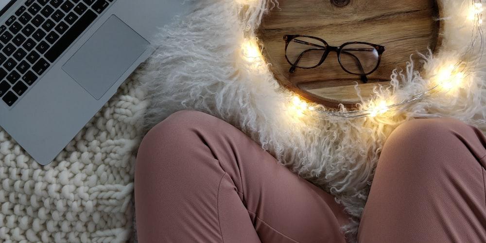 person wearing pink pants beside laptop