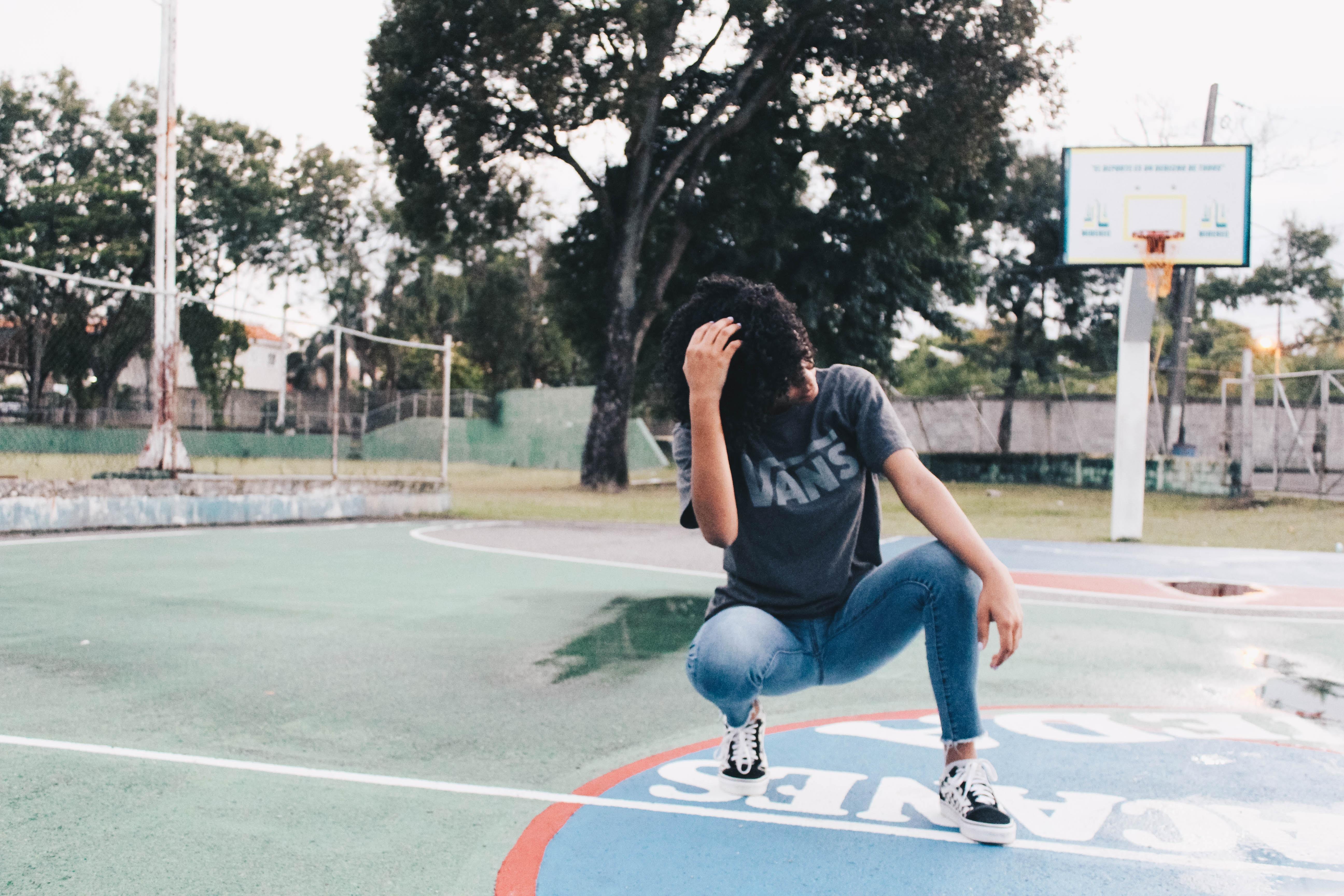 crouching woman wearing gray t-shirt on basketball court
