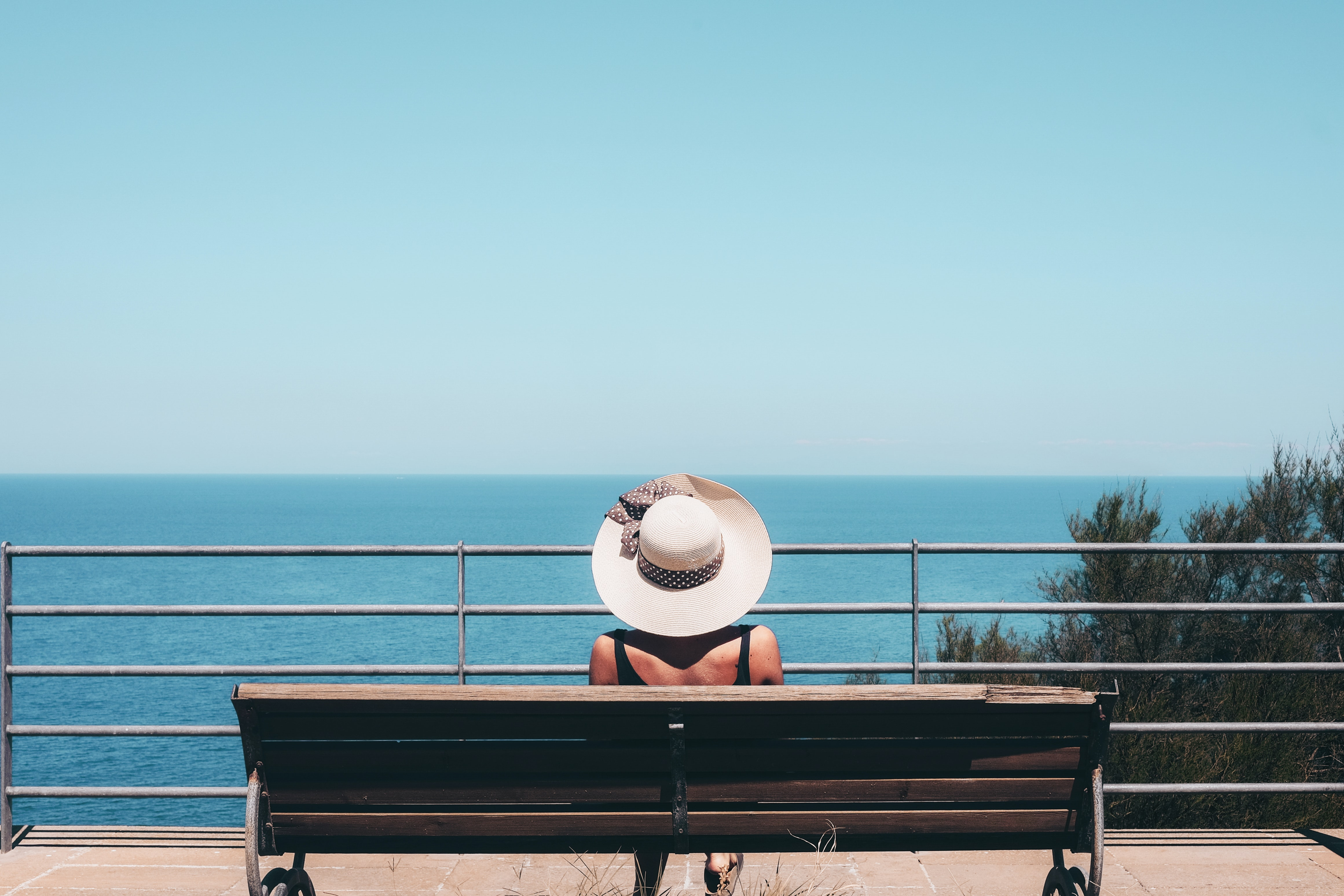 woman wearing white straw hat sitting on bench looking at sea
