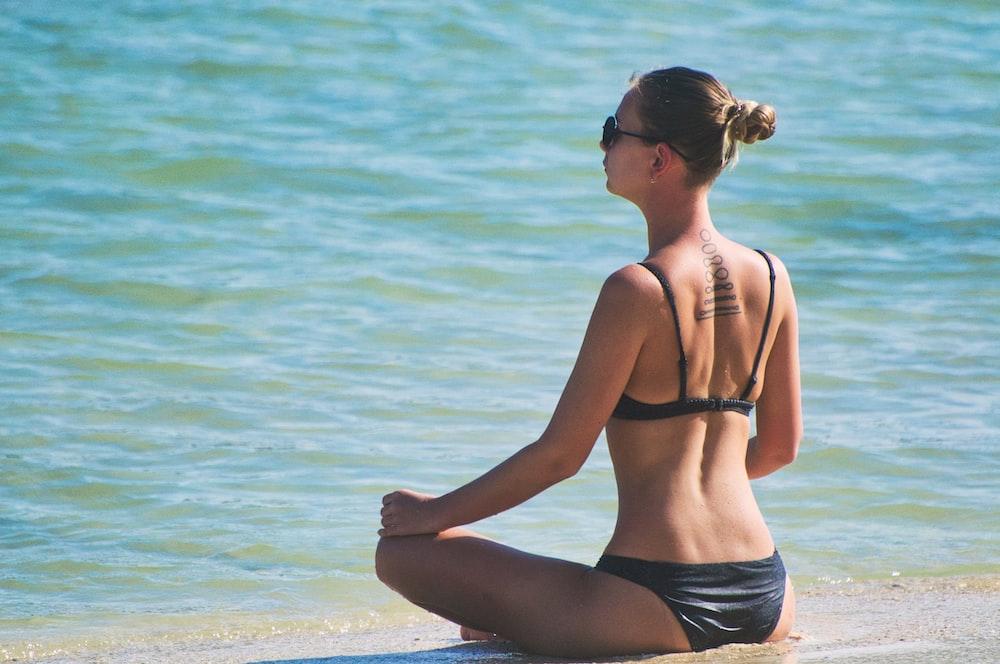 woman wearing bikini sitting by the seashore during daytime