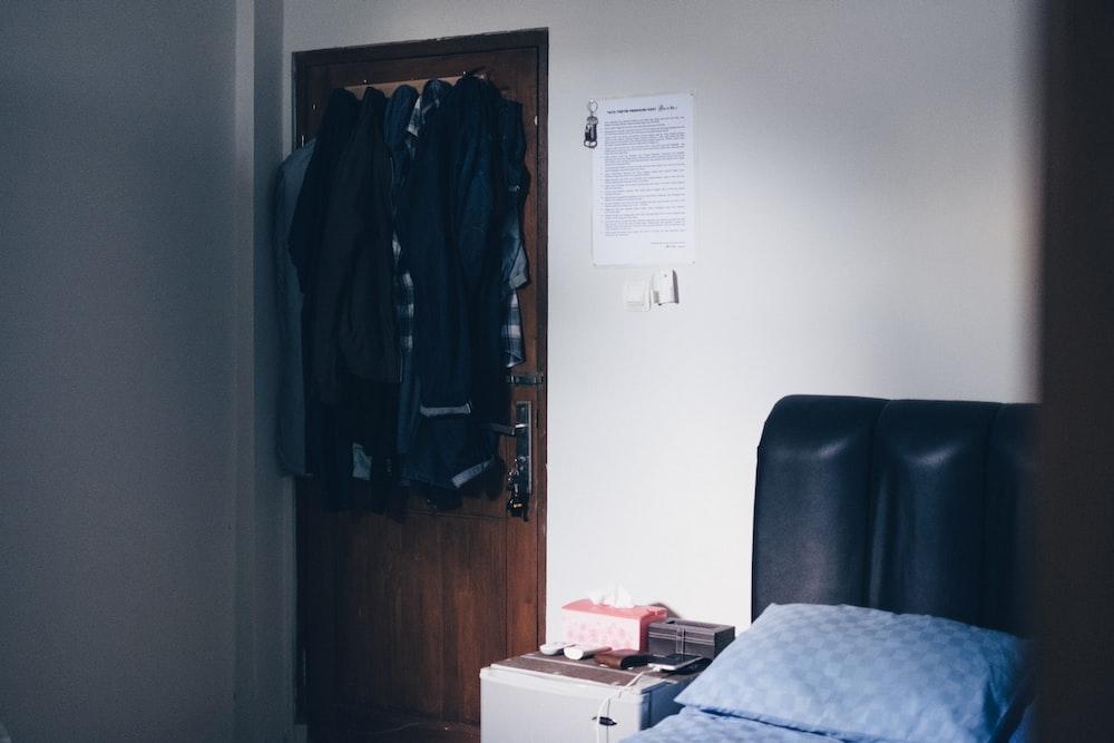 black apparels hanging on door