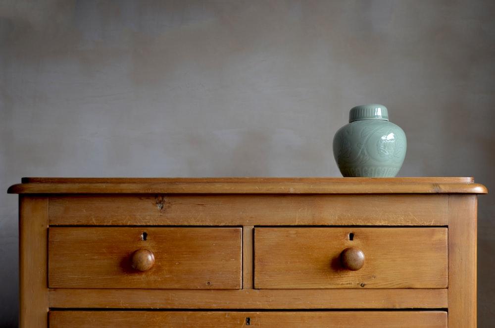 blue ceramic vase on brown wooden darawer dresser