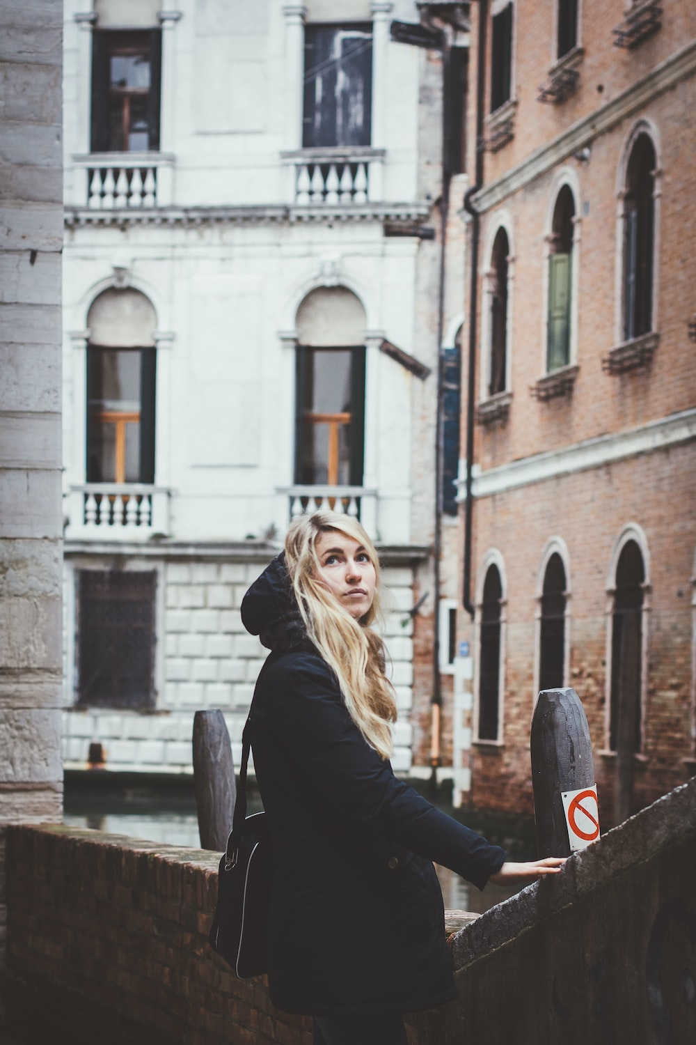 blonde-haired woman in black coat holding on concrete handrail