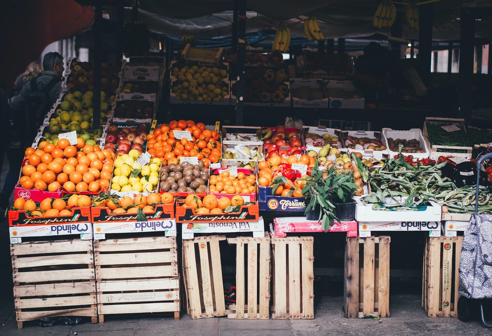 box of fruits on stand beside stall