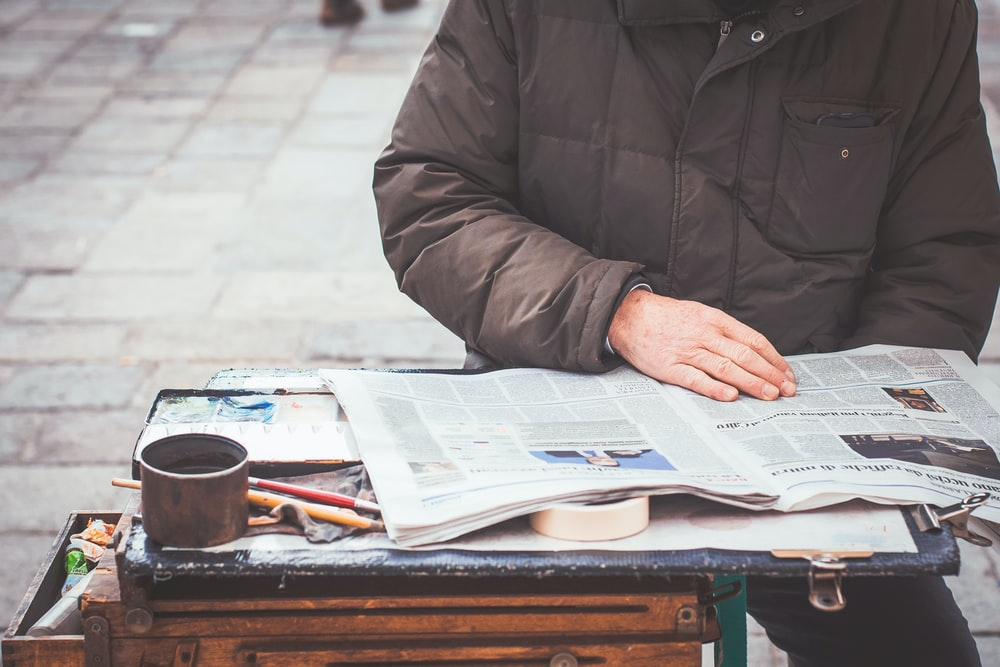 person wearing gray jacket reading newspaper