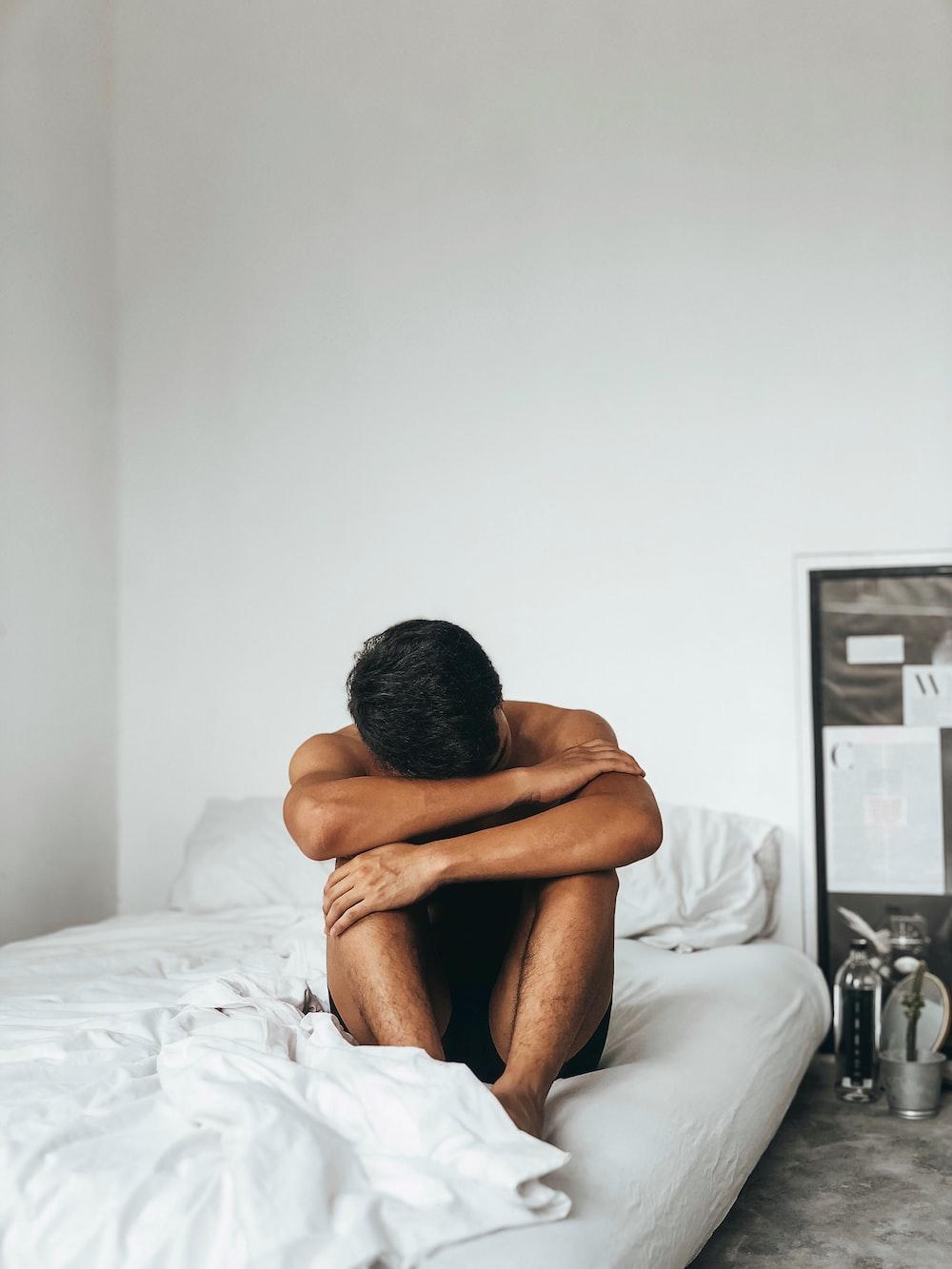 man sitting on bed