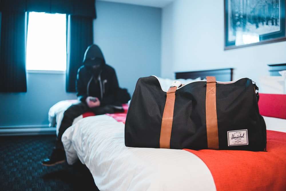 man in black hooded jacket sitting on bed near black and brown leather tote bag