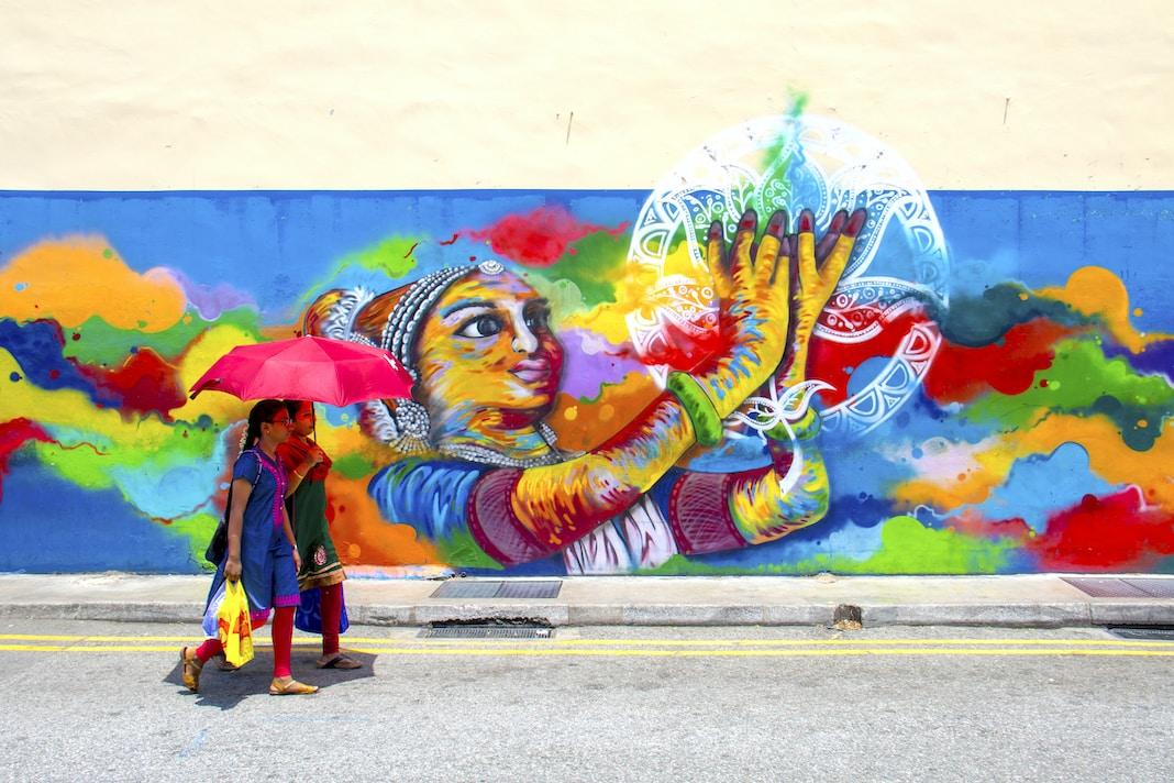 two girl holding umbrella while walking beside graffiti