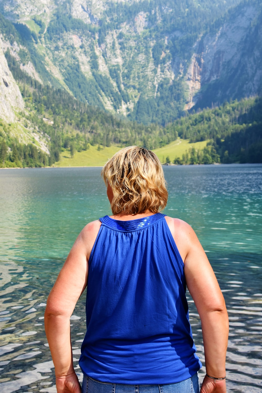 woman standing near body of water fronting mountain