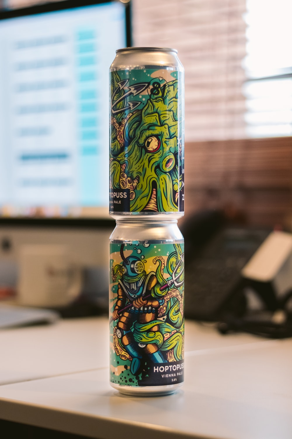 two green-and-gray cans on top of gray table