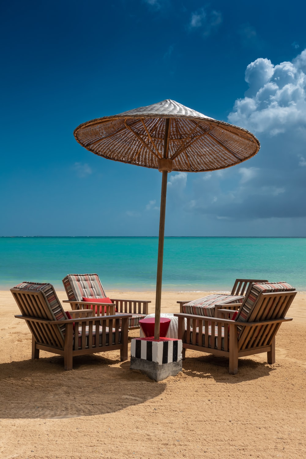brown wooden 5-piece patio set on sand during daytime