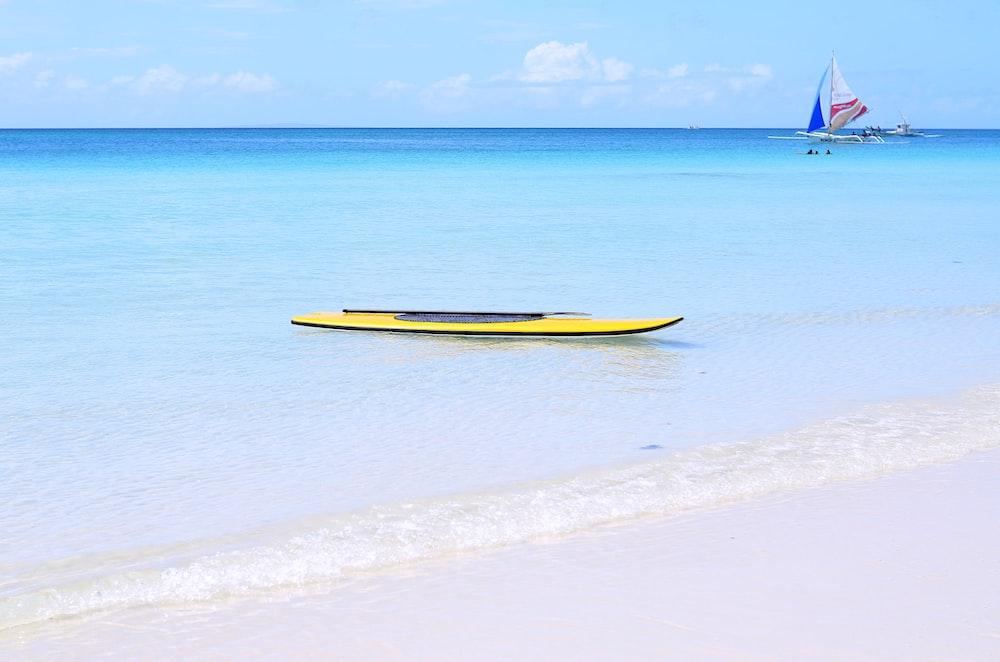 yellow kayak on ocean during daytime