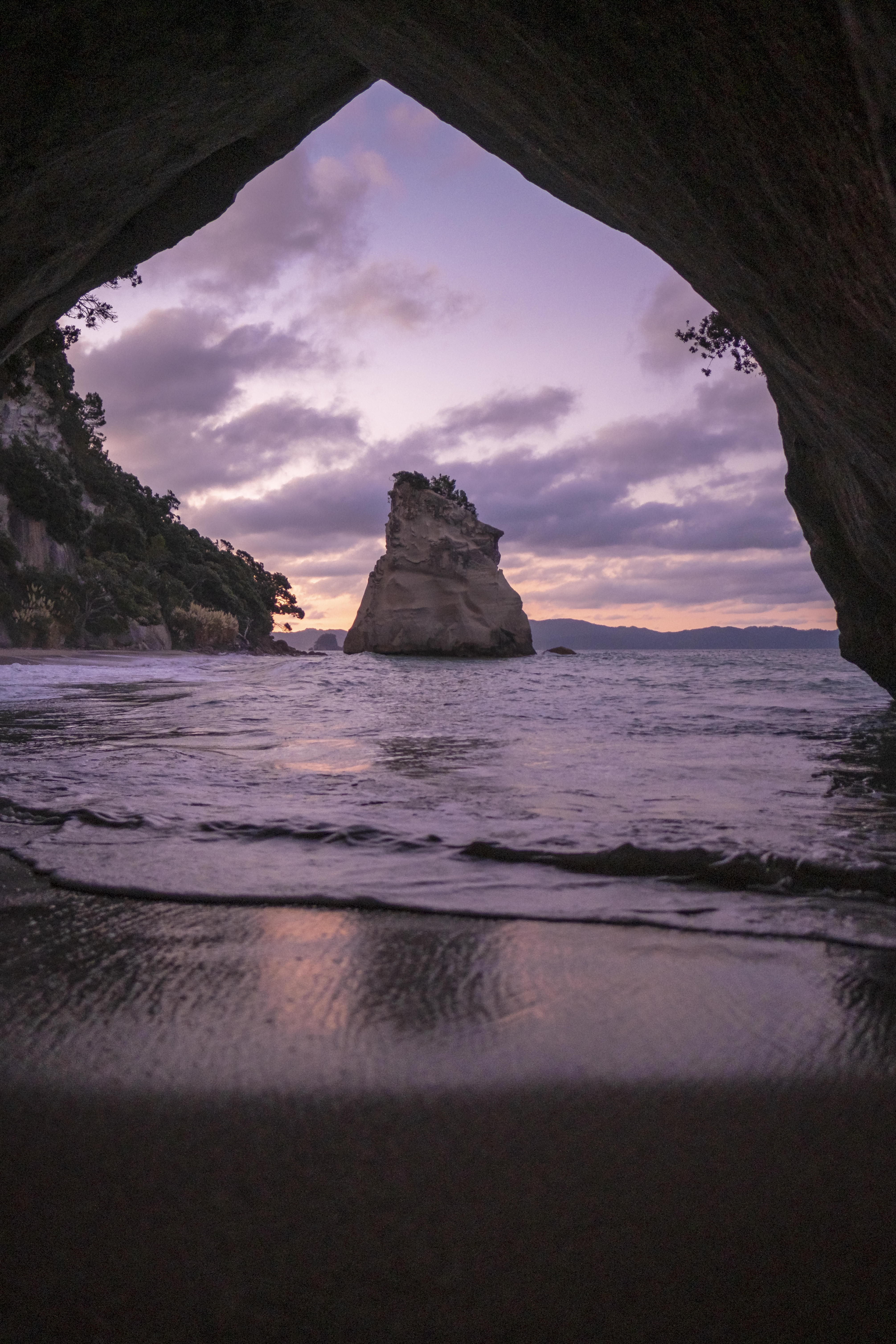 brown cave in front of shoreline