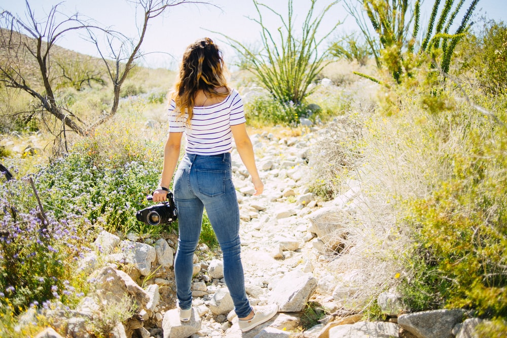woman standing on grey rock facing green plants
