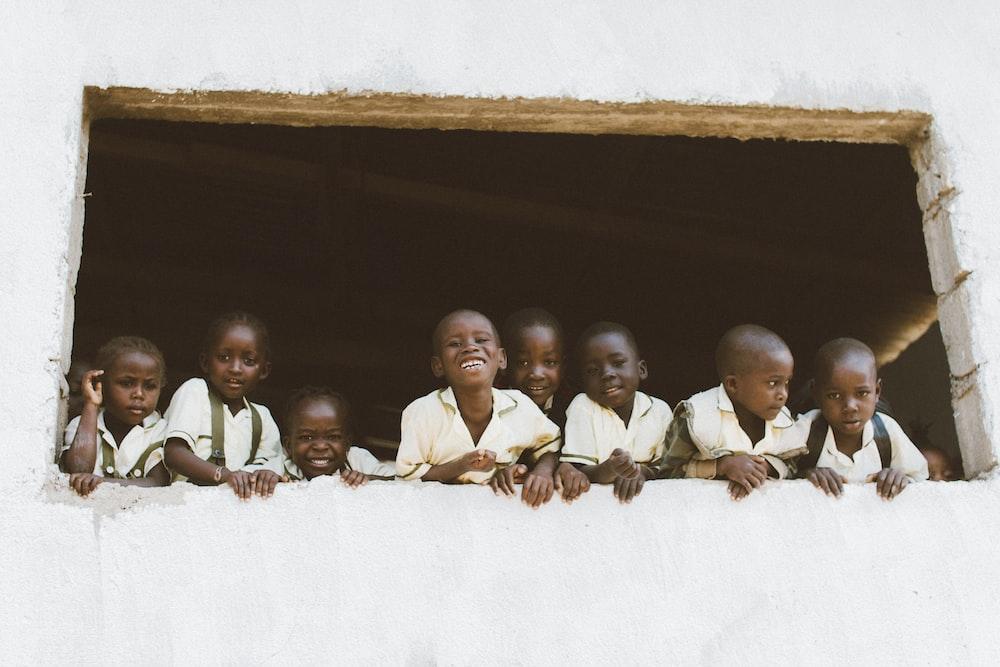 children standing in front of window