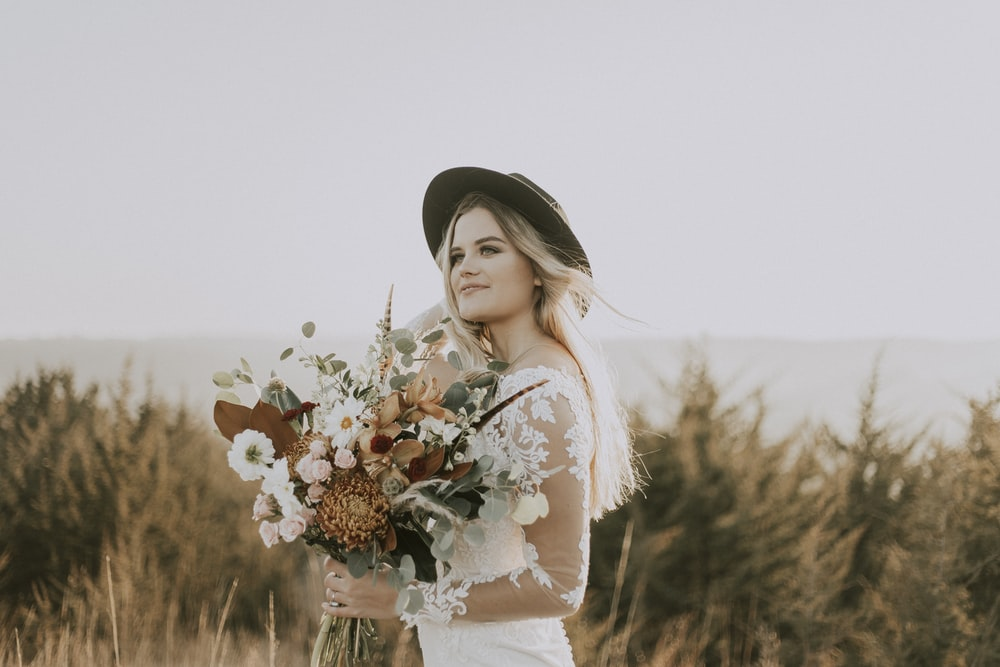 woman wearing hat, and white dress holding bouquet of flower