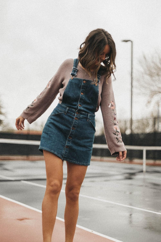 woman wearing blue denim jumper skirt over grey sweater