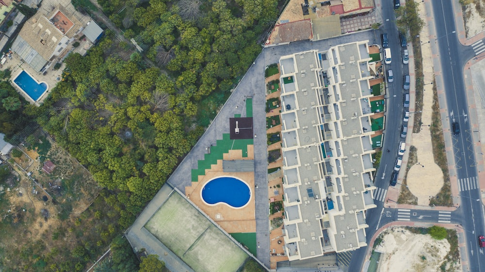 aerial photography of building between swimming pool and road during daytime