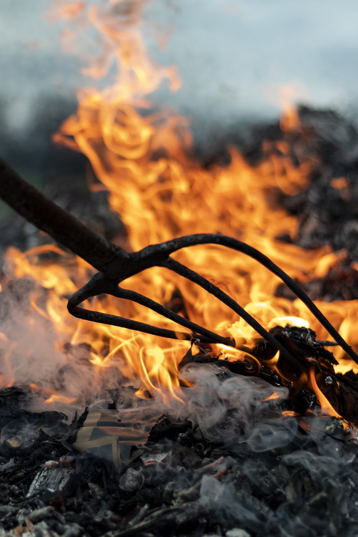 garden fork near burning wood during daytime