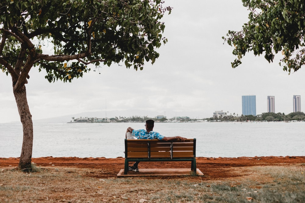 man sitting on bench facing calm sea during daytime