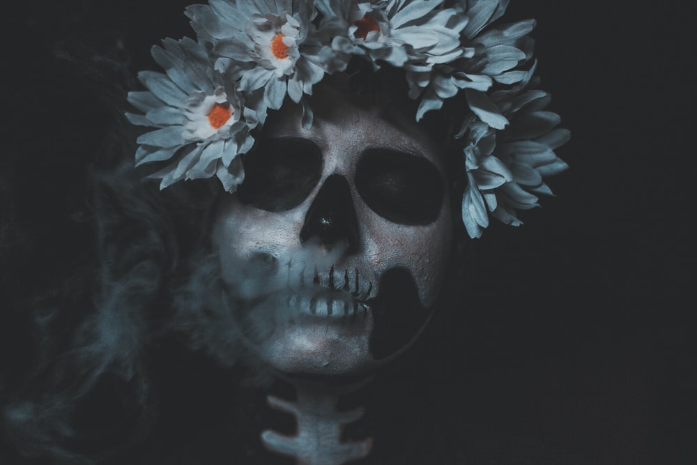 white and black skull with flower headband illustration