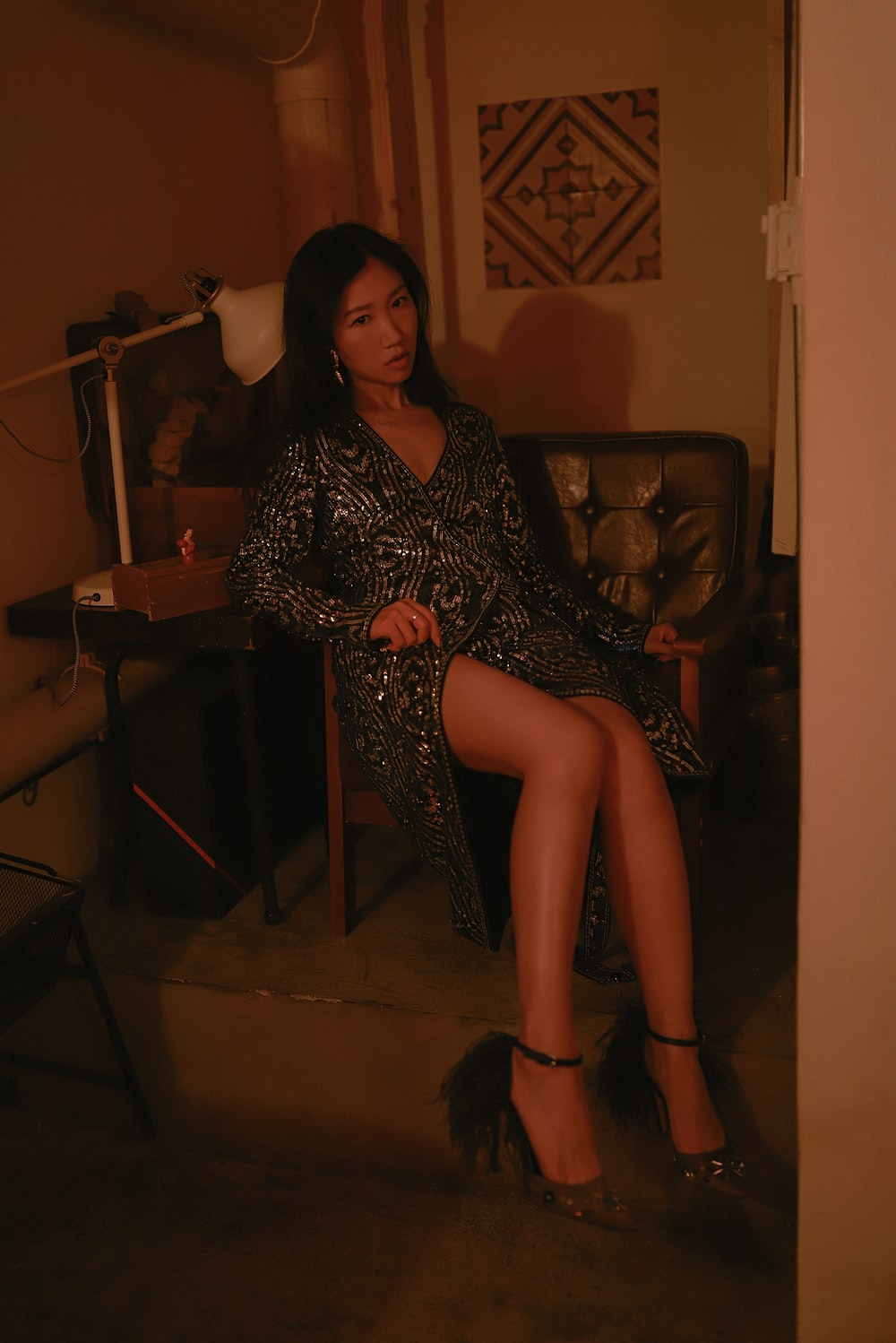 woman in black and blue beadred side slith dress sitting on chair