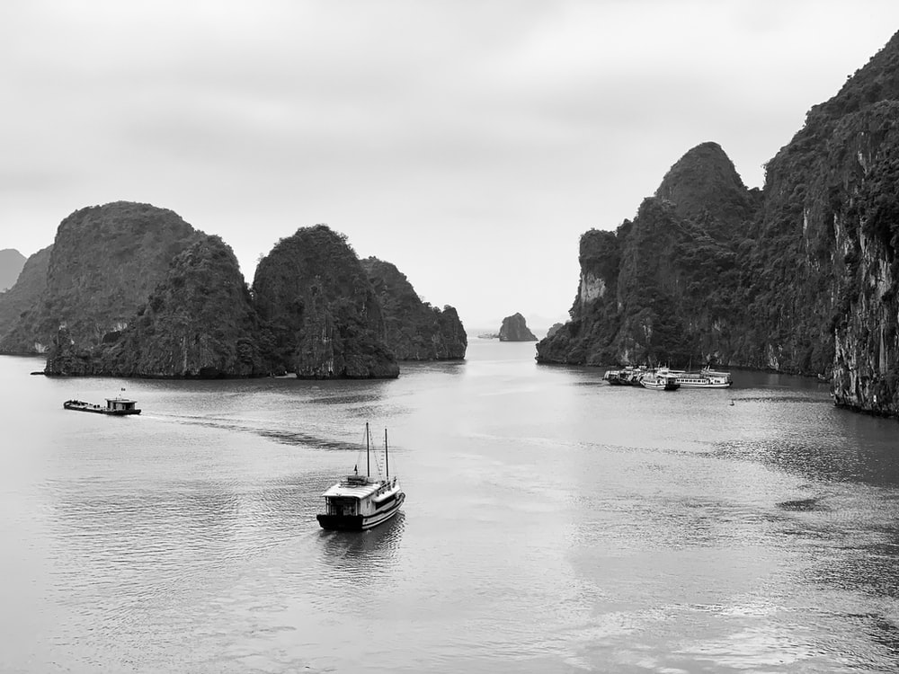 fishing boat sailing at the bay with rock islets