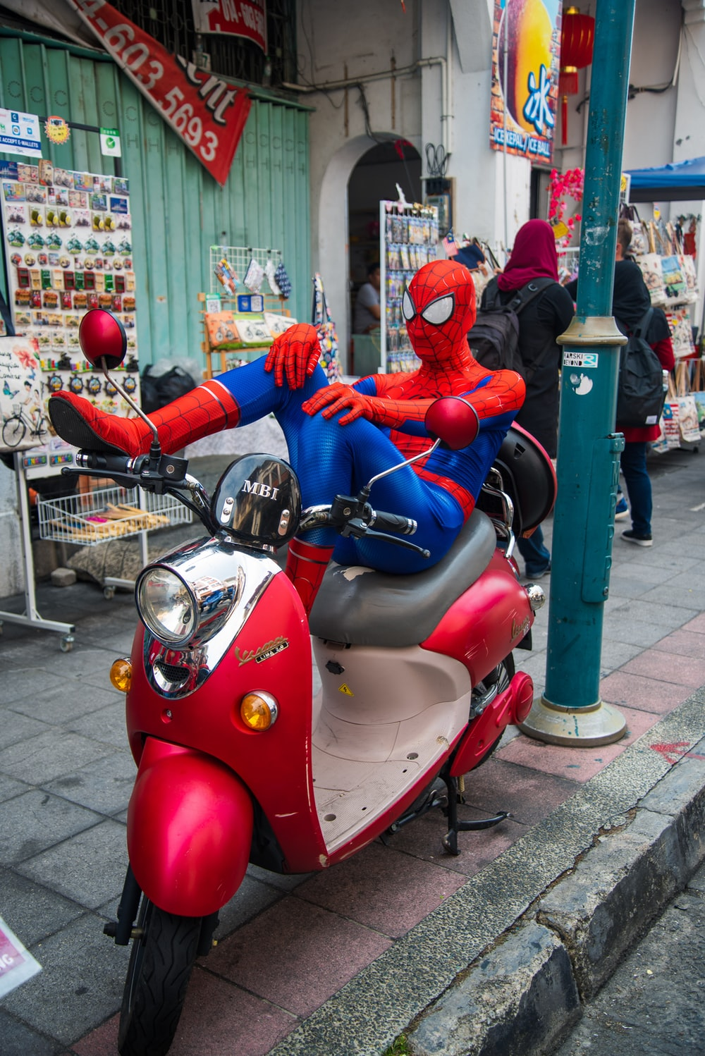 Spider-Man sitting on the motor scooter