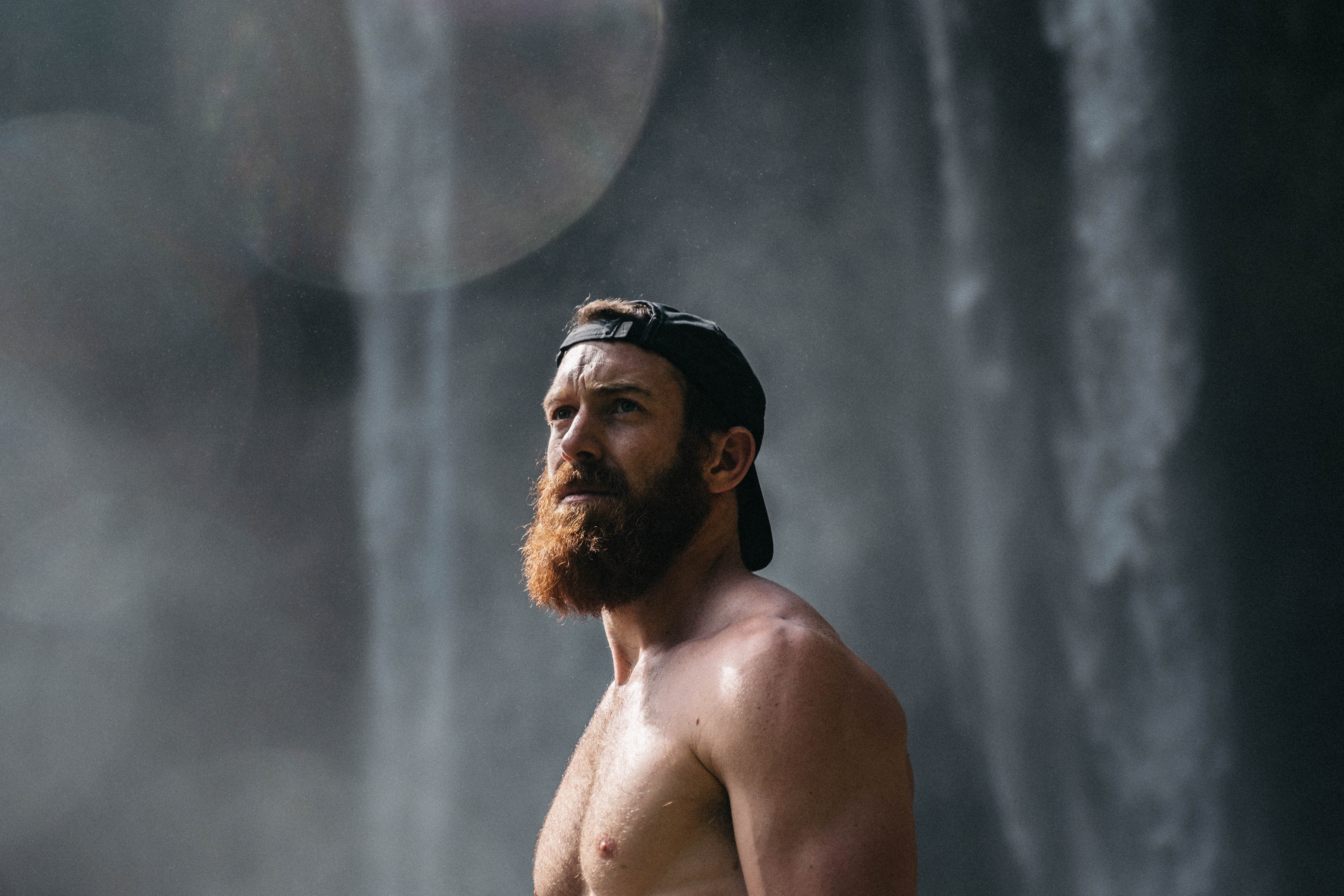 topless man wearing black fitted cap