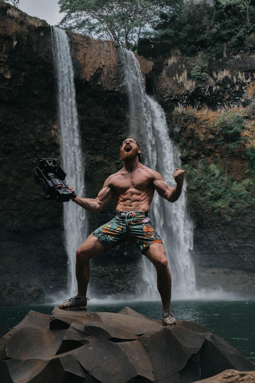 topless man screaming on top of rocks on waterfalls