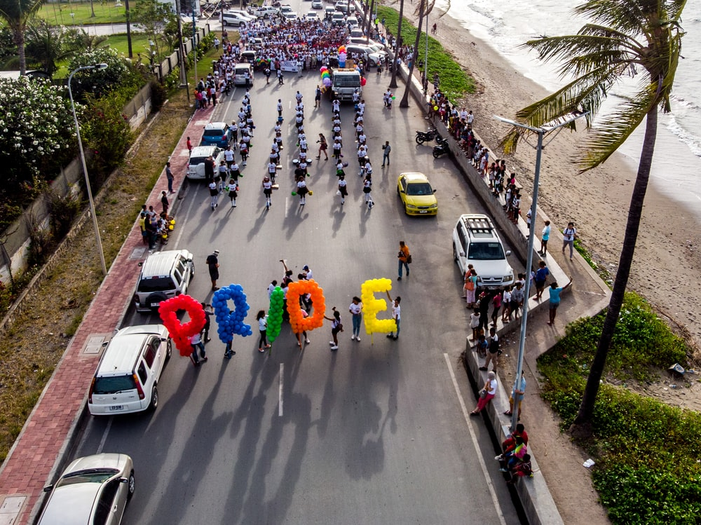 group of person walking on road carrying Pride balloons