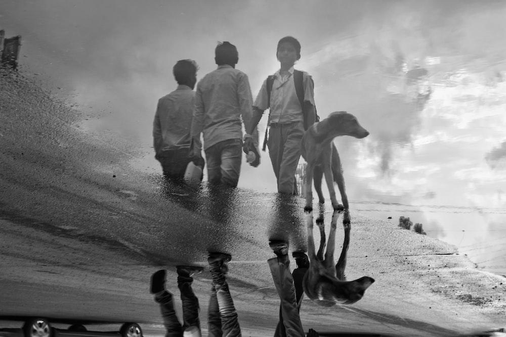 three men reflected on body of water beside door
