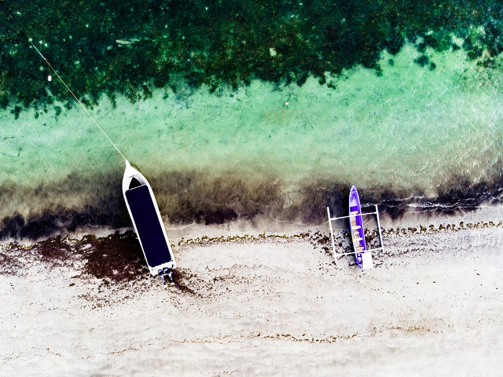 aerial photography of two boats on seashore