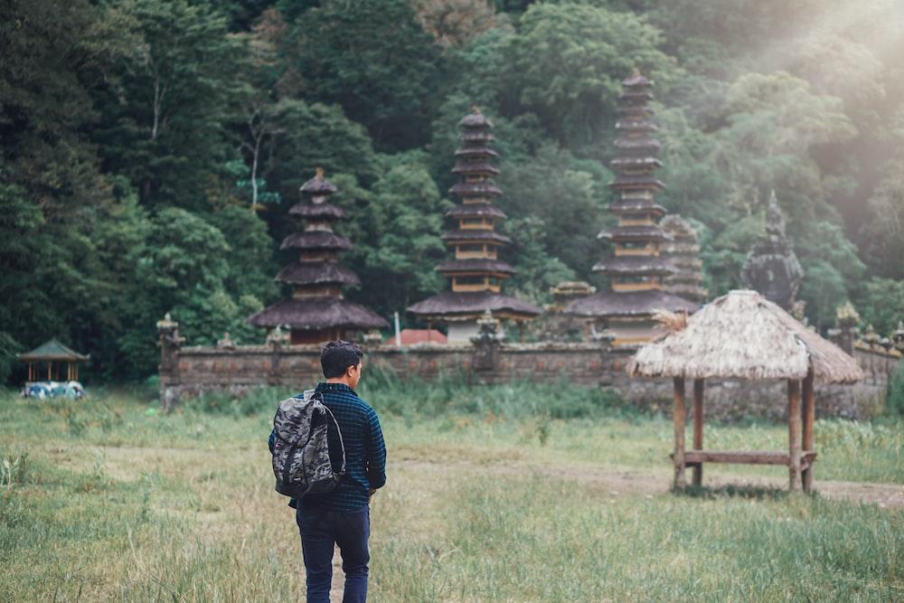 man walking on field near nipa hut