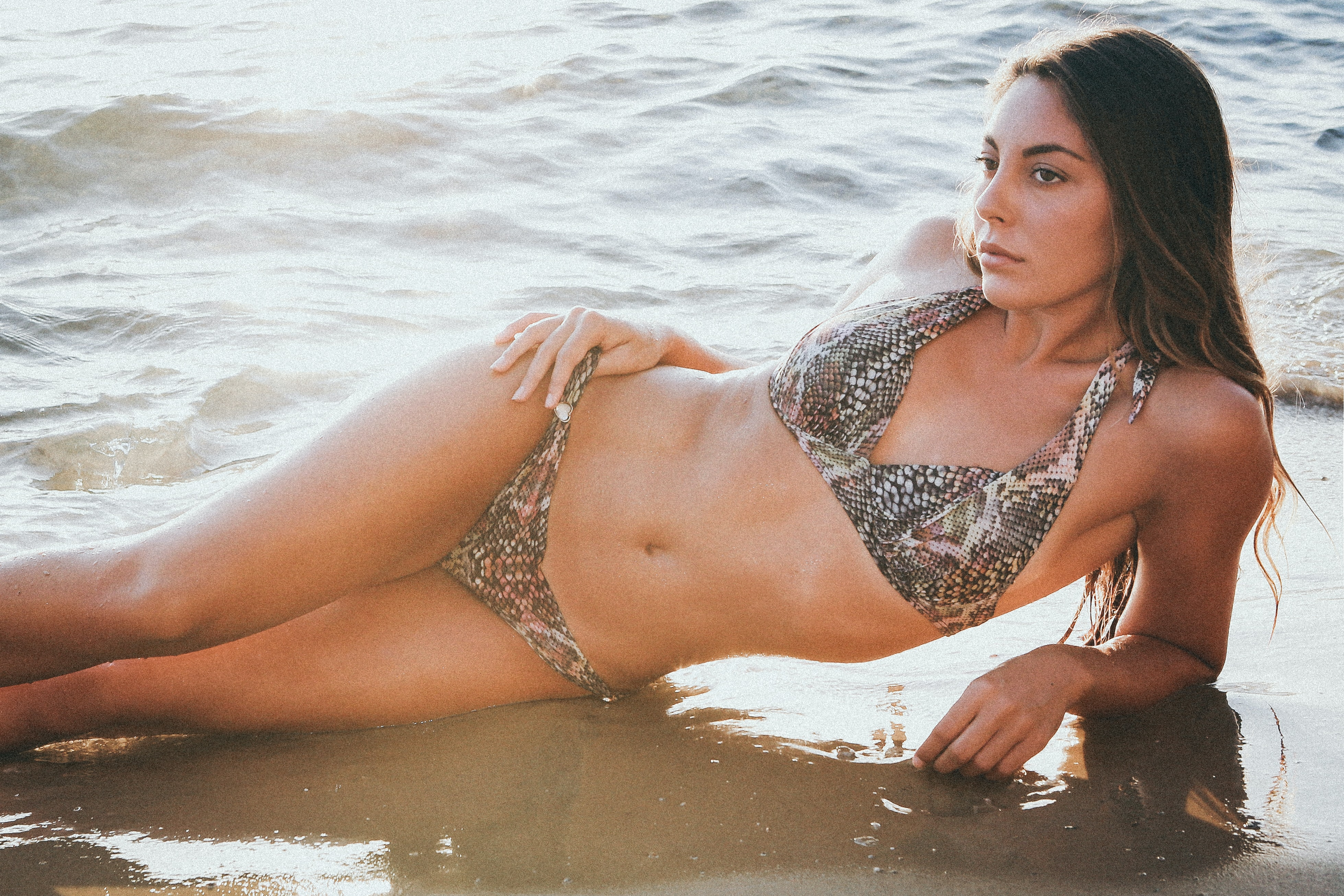 woman lying on wet sand wearing brown leopard bikini during daytime