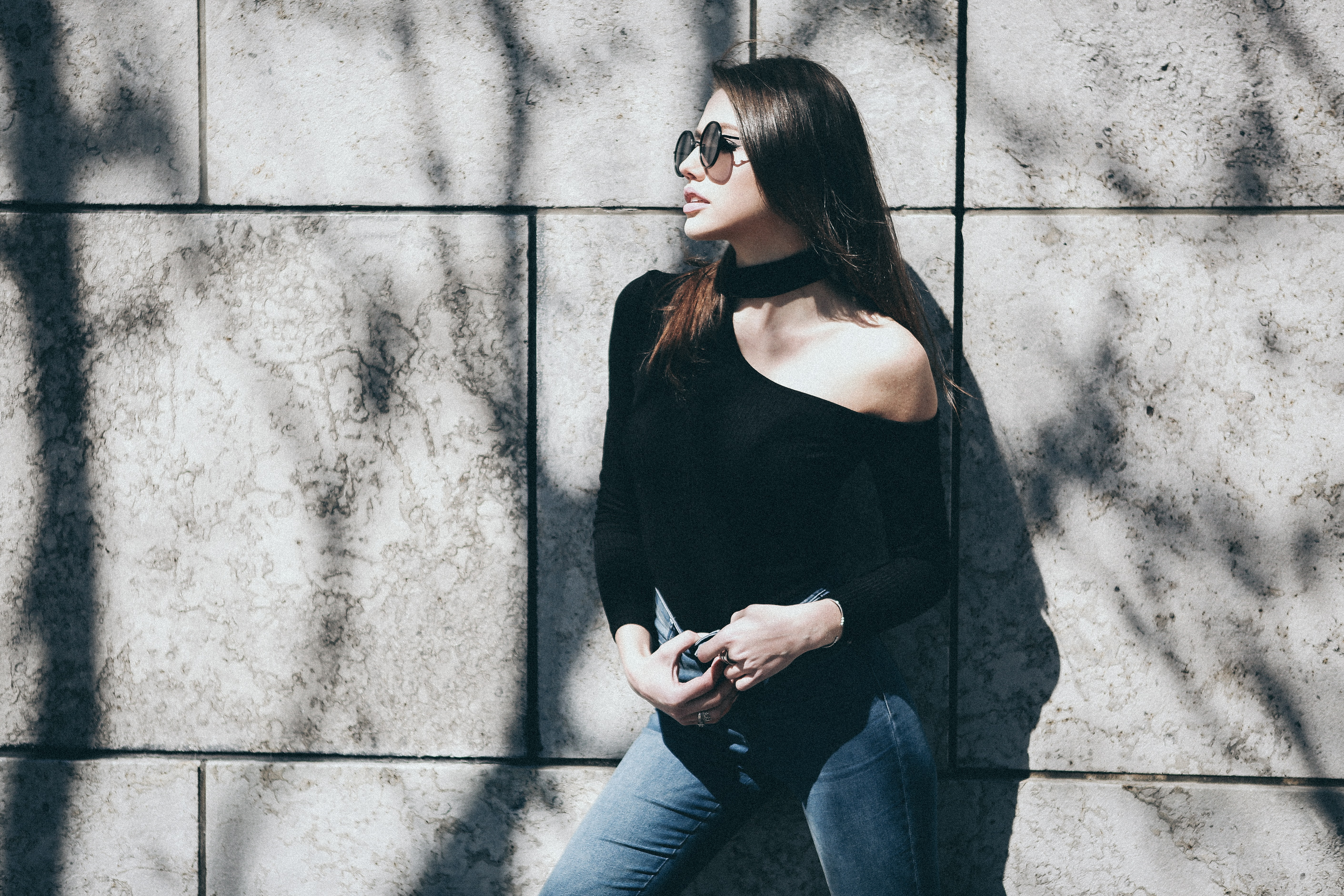 woman wearing black halter one-shoulder long-sleeved shirt and blue denim bottoms outfit during daytime
