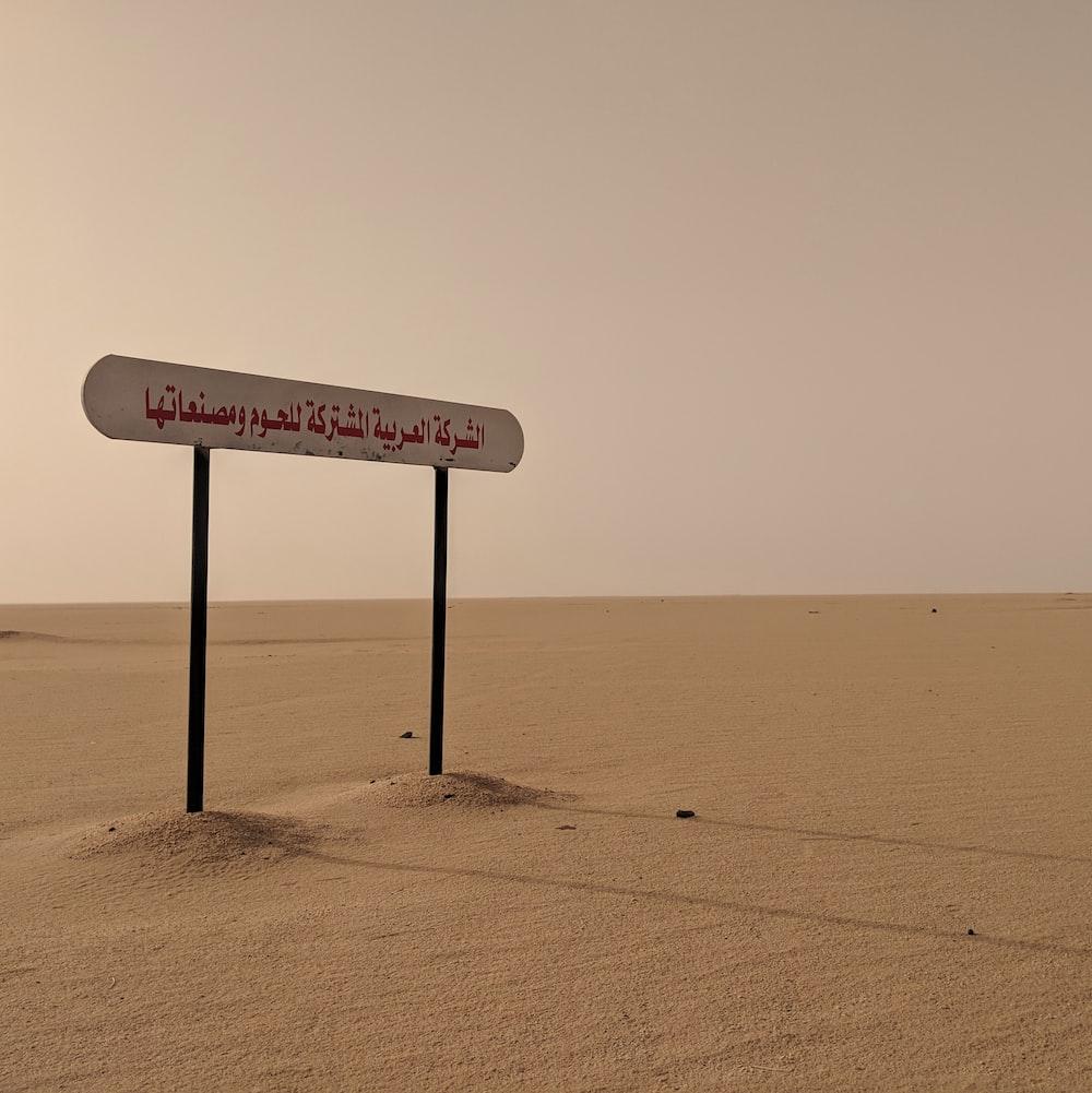 white wooden signage on the desert