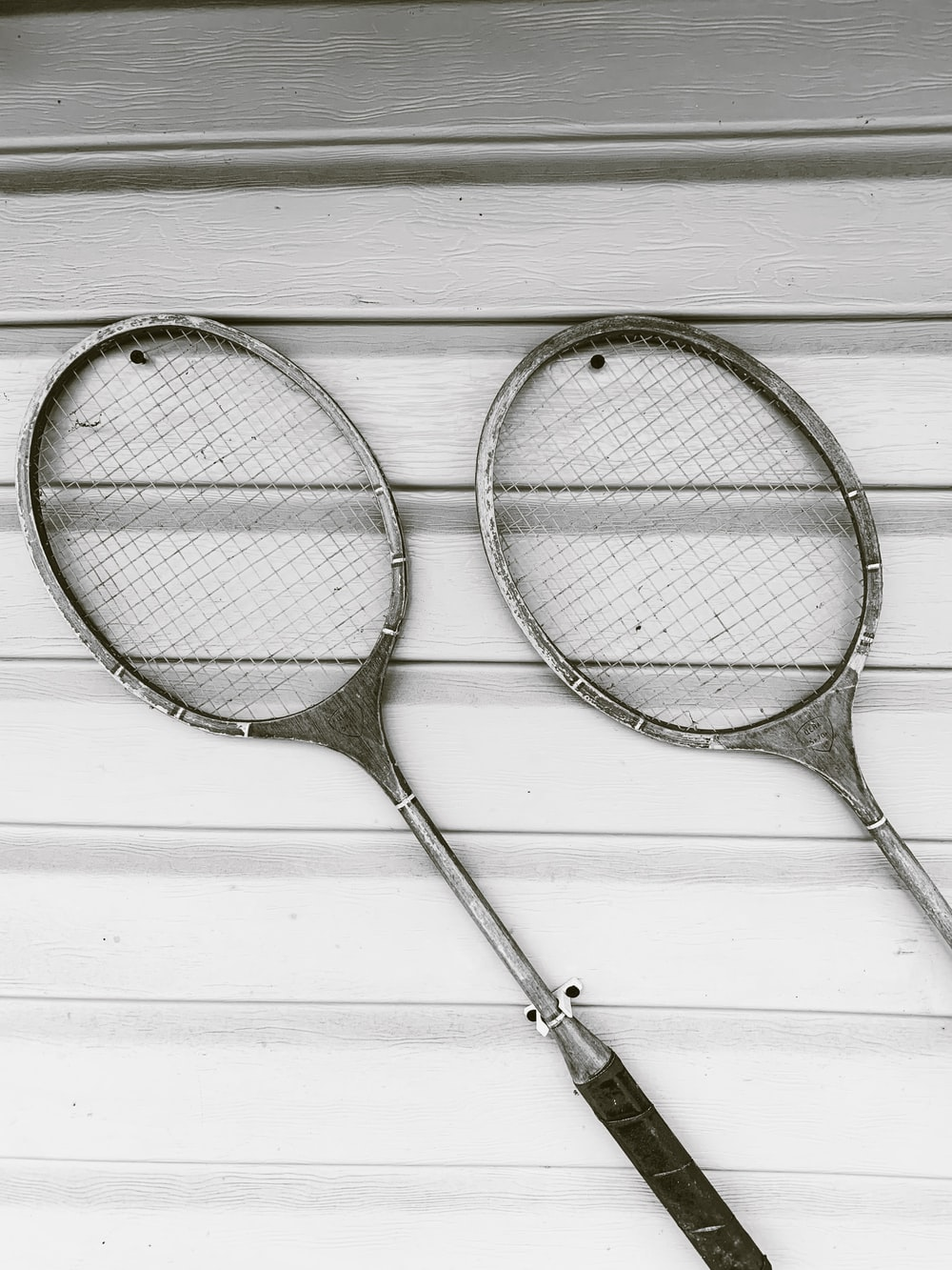 two gray badminton rackets on white wooden surface