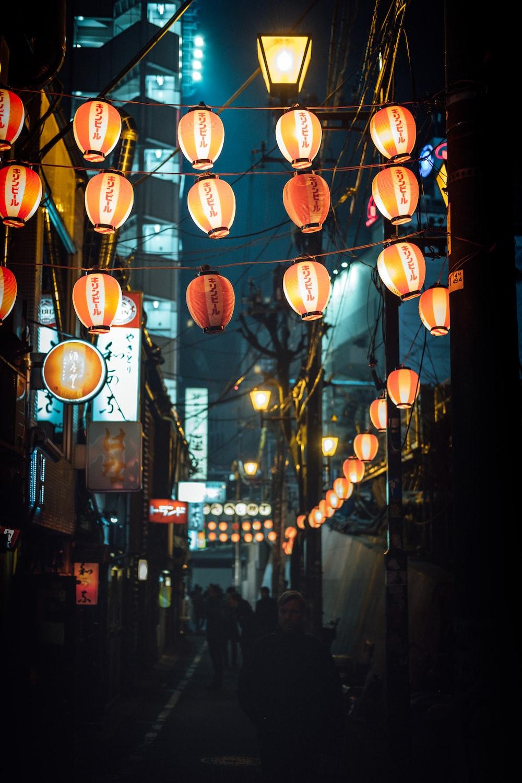 people walking pass under lighted lanterns