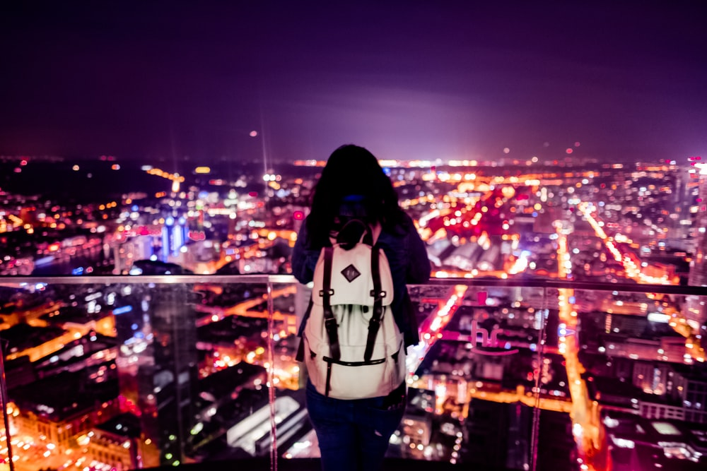 person standing nearrailings viewing city at night